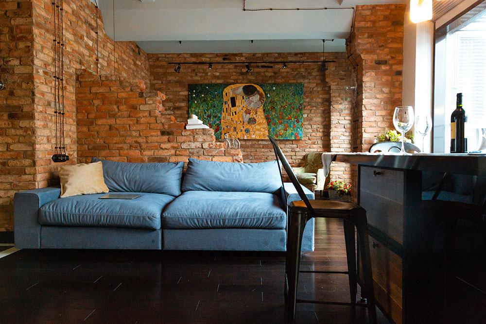 Яркие рыжие стены из настоящего кирпича, наружная проводка - непривычное, но очень уютное решение для жизни