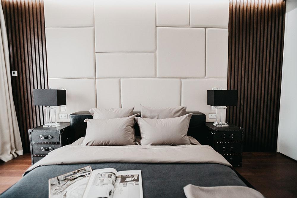 Мягкое кожаное изголовье кровати дополнено довольно брутальной известной мебелью
